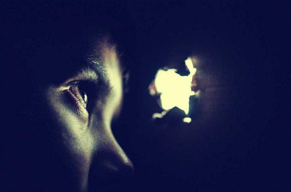 Ein Auge schaut durch eine Öffnung in der Wand