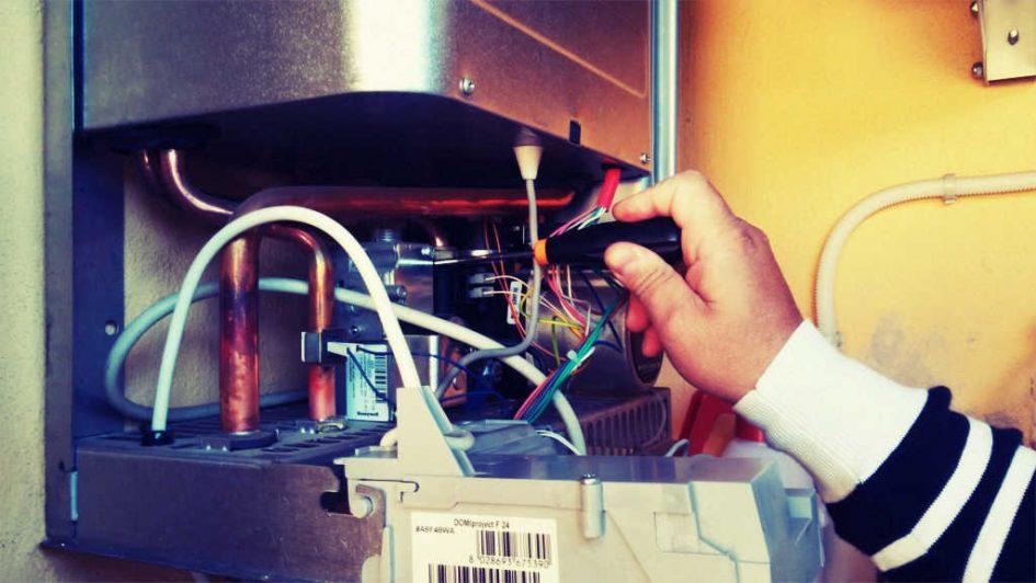 ein Mann repariert einen Boiler